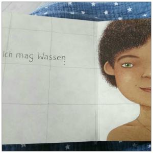 """Ein Kind mit krausem dunkelbraunem Haar und grünen Augen, neben dem Kind steht """"Ich mag Wasser"""""""